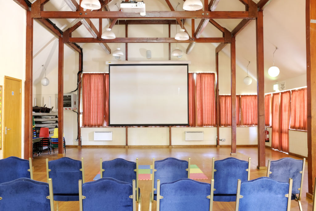 Hall interior with theatre seating and projector screen