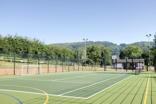 Sports pitch with tennis, football, netball, and basketball markings.